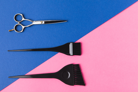 top view of hairdressing tools, on pink and blue diagonal background