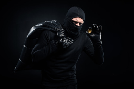 Man in balaclava holding plastic bag with cash and bitcoin Stock Photo