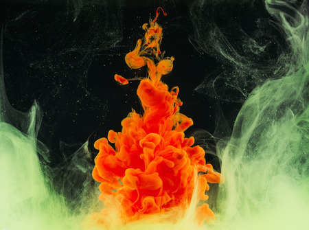 Close-up view of bright abstract orange ink explosion on black