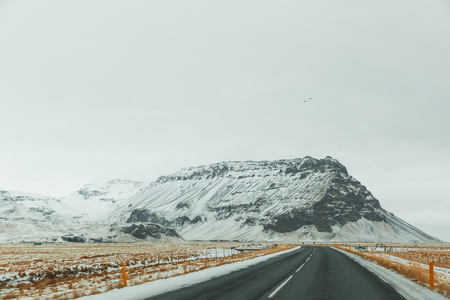 Empty asphalt road and majestic snow-covered mountains in Iceland 写真素材