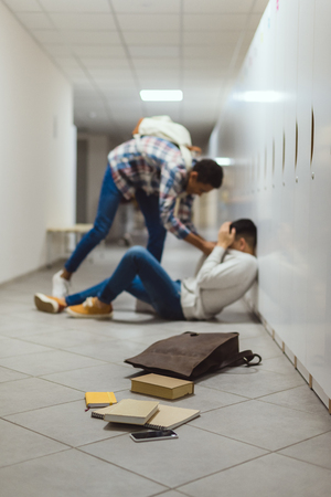 Schoolboy being bullied by classmate in school corridor under lockers with spilled books from backpack on floor Stock Photo