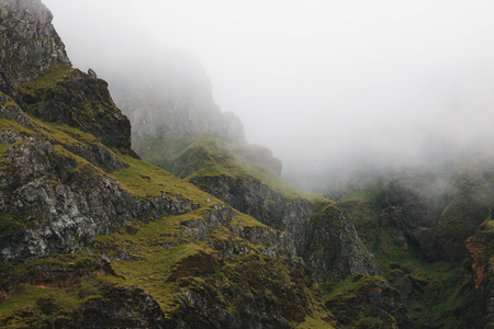 Beautiful rocks covered with green moss in fog, Iceland