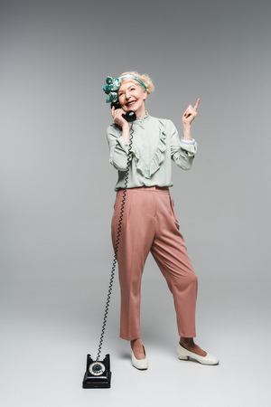 Smiling senior woman talking by vintage phone and pointing up on grey background Stock Photo