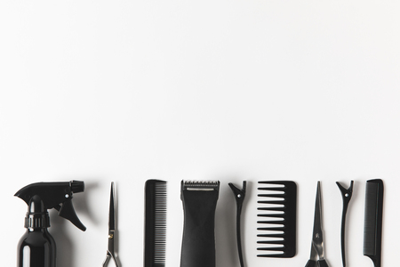 Top view of hair clipper and hairdressing tools in row, on white background
