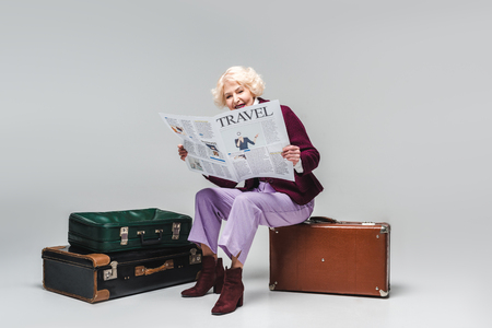 Beautiful senior woman sitting on vintage suitcase and reading travel newspaper on grey background
