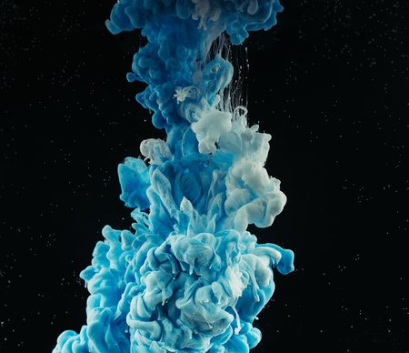 Close-up view of abstract blue and white flowing paint on black background