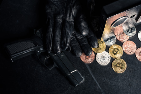 Black gloves and gun by open safe with bitcoin Stock Photo - 110794409