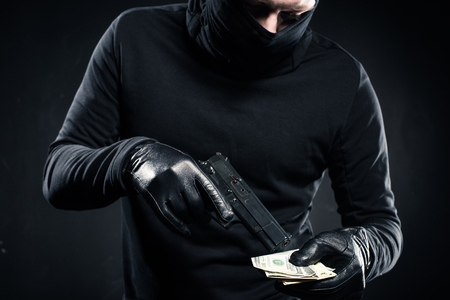 Man in black balaclava holding gun and dollars Stock Photo