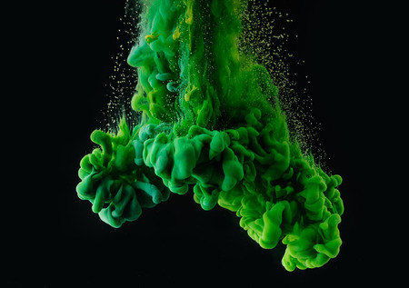 Bright green abstract ink explosion on black background