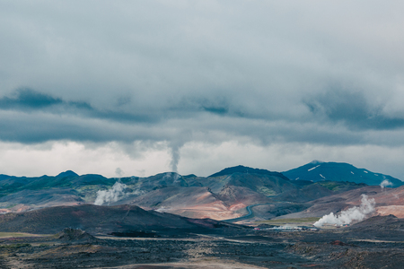 Majestic Icelandic landscape with mountains and steam from hot springs at cloudy day Imagens