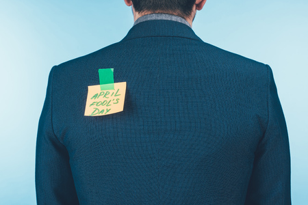 Back view of businessman in suit with note with April fools day lettering on back, April fools day concept