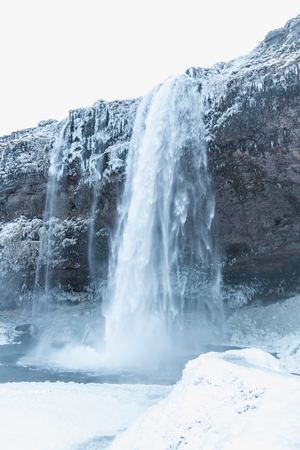 beautiful landscape with scenic Seljalandsfoss waterfall and snow-covered rocks in iceland