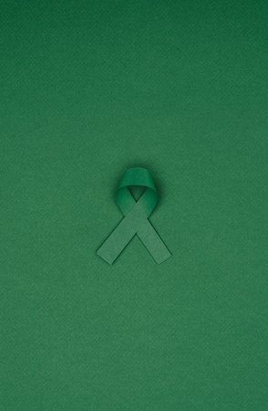 close up view of green ribbon isolated on green tabletop, world health day concept Stock Photo