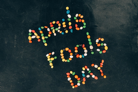 Top view of arranged candies in Aprils fools day lettering isolated on black tabletop background