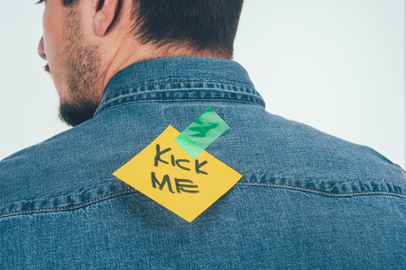 Back view of man with note on sticky tape with kick me lettering on back, April fools day holiday concept Stock Photo