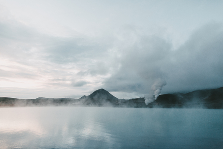 Majestic Icelandic seacoast with rocky mountains and steam from hot springs