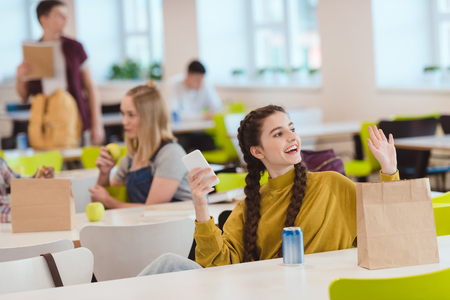 Smiling teen schoolgirl sitting at school cafeteria and greeting friend