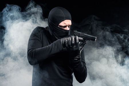 Robber in balaclava and gloves aiming with gun in clouds of smoke