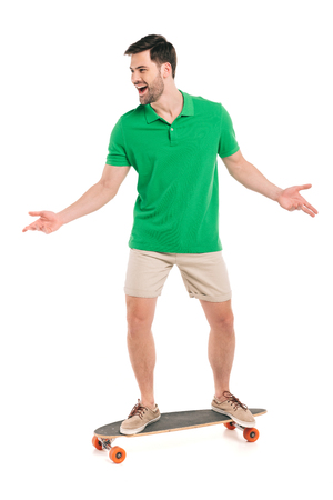 Cheerful young man in shorts and polo shirt standing on skateboard isolated on white background