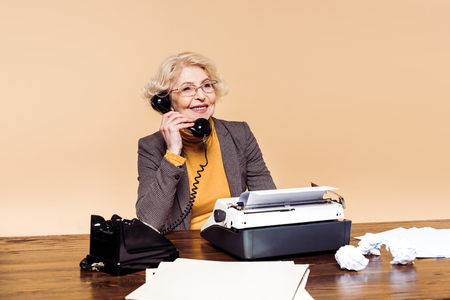 Fashionable stylish senior woman in eyeglasses talking on rotary phone at table Banco de Imagens