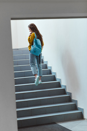 Rear view of schoolgirl with backpack walking upstairs Stock Photo
