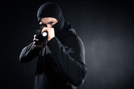 Burglar in balaclava aiming with gun and flashlight Stock Photo