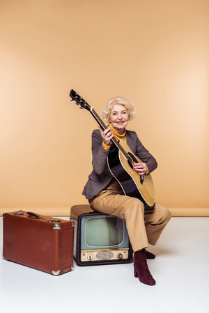 Senior woman with acoustic guitar sitting on vintage television near old suitcase Foto de archivo