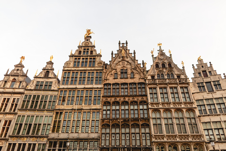 Low angle view of beautiful buildings with statues in historic quarter of Antwerp, Belgium