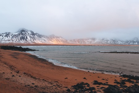 Spectacular view of snow-covered mountains, fjord and rainbow in Iceland Stock Photo