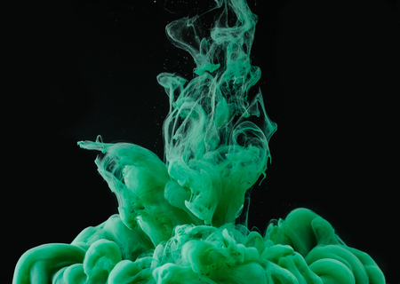 Close-up view of green ink explosion on black background