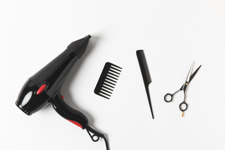 Top view of hair dryer, combs and scissors, on white background Фото со стока