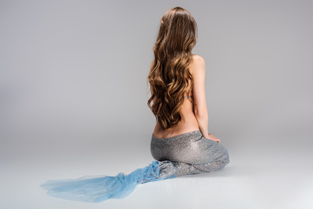 Back view of woman with mermaid tail and long hair, isolated on grey background