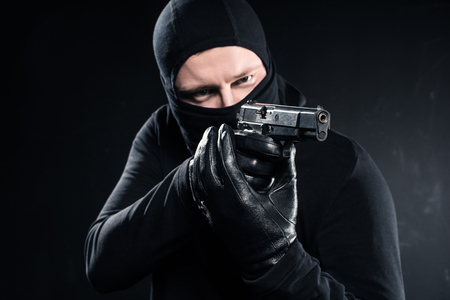 Male robber in balaclava aiming with gun on black background