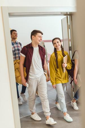 Groupe multiethnique d'élèves du secondaire marchant dans le couloir de l'école pendant la pause Banque d'images