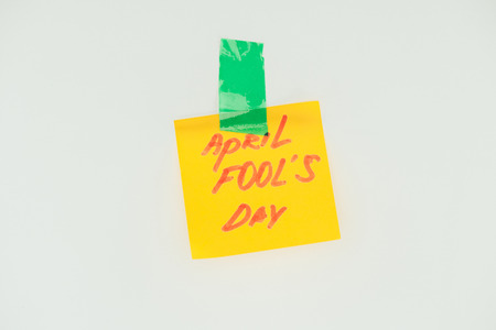 Close up view of note with April fools day lettering and sticky tape isolated on grey, April fools day concept Stok Fotoğraf