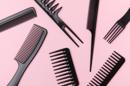 Top view of black combs, isolated on light pink Фото со стока