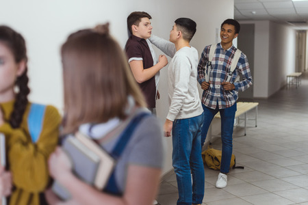 Schoolboy being bullied by classmates in school corridor while schoolgirls passing away Stock Photo