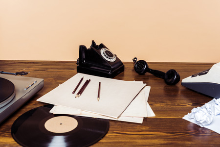Rotary phone, vinyl disc, record player and typewriter on wooden table Banco de Imagens