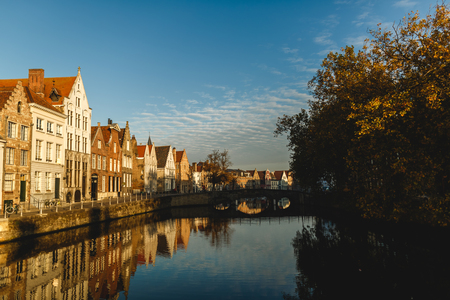 Beautiful traditional houses reflected in calm water of canal, Brugge, Belgium