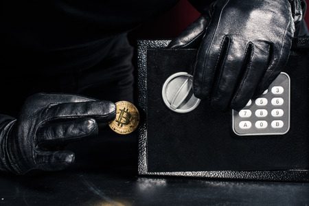 Male hand stealing golden bitcoin from safe Stock Photo - 110824935
