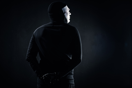 Rear view of male criminal in mask and balaclava