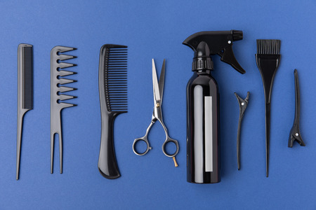 Flat lay with black hairdressing equipment, isolated on blue background Фото со стока