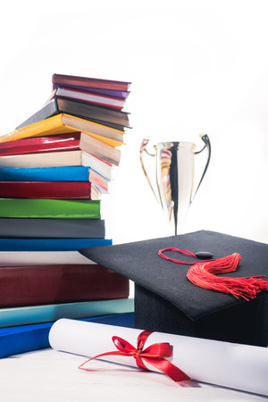 Graduation cap and diploma in front of books and trophy cup