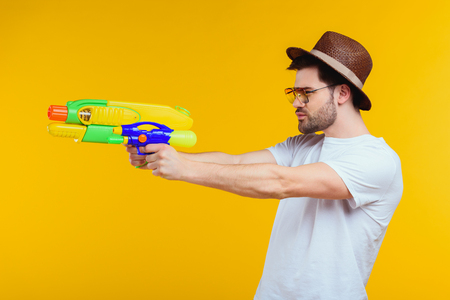 Side view of young man holding water gun and looking away isolated on yellow background