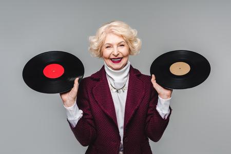 Happy stylish senior woman holding vinyl discs isolated on gray background