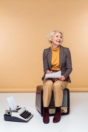 Smiling stylish senior woman writing on paper sitting on vintage television near typewriter Stock Photo
