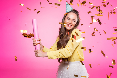 Attractive woman with party hat under falling confetti isolated on pink background