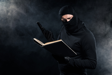 Man in black balaclava holding gun and reading book