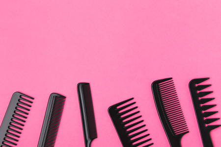 Top view of black combs, isolated on pink background Фото со стока
