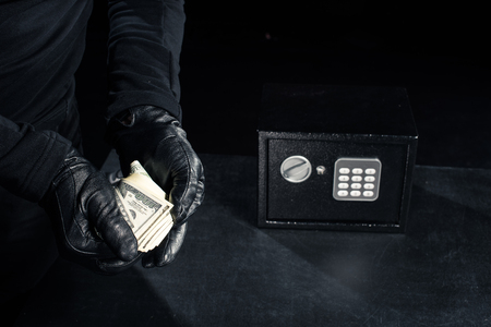 Close-up view of robber in gloves taking dollars from safe